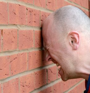 a man banging his head agaist the wall in frustration